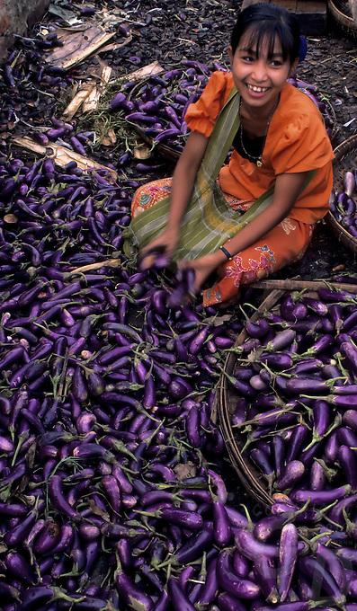 A girl vendor in the main Yangon Market, sorting and selling Eggplants,Burma, Myanmar