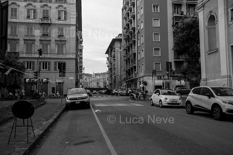 """Via Caffa and Piazza Alimonda, renamed as Piazza Carlo Giuliani, Ragazzo. <br /> <br /> The photos of this story are presented appositely in Black And White to show to the audience """"the Places"""" where the majority of - the already mentioned (see above) - """"suspensions of fundamental rights […] such as freedom of expression, freedom of movement, the right to physical integrity"""" (2.) happened, including Piazza Alimonda, Via Tolemaide, Corso Torino, Via Caffa, Viale Delle Brigate Partigiane, Corso Guglielmo Marconi, Scuola Diaz (the Diaz School). Unfortunately, the Bolzaneto's barracks couldn't be documented due to the distance from Genoa's city centre. This police station was used as a temporary prison for the people taken away from the Diaz School, where physical and psychological tortures and humiliations where perpetrated by officers, including managers and supervisors.<br /> <br /> All Clickable Links:<br /> <br /> Footnotes, Links, Sources:<br /> <br /> 1. http://bit.do/fRvdg<br /> 2. http://bit.do/fRvdi<br /> 3. http://bit.do/fRvdj<br /> 4. http://bit.do/fRvdn<br /> 5. http://bit.do/fRvdo<br /> 6. 12.10.18 - Sulla Mia Pelle: Stefano Cucchi's Film Screening At CSOA La Strada http://bit.do/fRvdr<br /> 7. http://bit.do/fRvdt & http://bit.do/fRvdu<br /> 8. http://bit.do/fRvdv & http://bit.do/fRvdw & http://bit.do/fRvdx<br /> 9. http://bit.do/fRvdz<br /> 10. http://bit.do/fRvdA<br /> 11. http://bit.do/fRvdB<br /> http://www.veritagiustizia.it/docs/G8_2021_prog_ITA.pdf http://www.veritagiustizia.it/documenti.php & http://www.veritagiustizia.it/doc_eng/<br /> https://www.carlogiuliani.it<br /> https://en.wikipedia.org/wiki/Death_of_Carlo_Giuliani<br /> The bloody battle of Genoa by Nick Davies (Source, The Guardian, 2008): https://www.theguardian.com/world/2008/jul/17/italy.g8"""