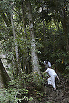 A guide helps a woman up a steep section of the Blue Creek Cave Trail near Punta Gorda, Belize