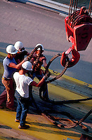 Oil workers with a crane.