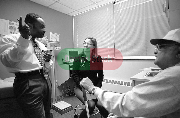 Young female internal medicine resident physician and Spanish translator discussing personal health issues with elderly African-American male in examination room