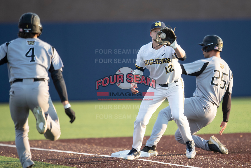 Michigan Wolverines third baseman Riley Bertram (12) receives the ball Western Michigan Broncos baserunners Ryan Missal (4) and Ethan Hajdukovic both arrive at the base on March 18, 2019 in the NCAA baseball game at Ray Fisher Stadium in Ann Arbor, Michigan. Michigan defeated Western Michigan 12-5. (Andrew Woolley/Four Seam Images)