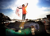 """Sabina stands on the roof of one of the shacks in the slum where she lives holding up a brightly coloured scarf..Sabina is 9 years old and lives with her parents and brother in a slum in Delhi. Her father is a rickshaw driver and the family has very little money. The slum where they live is dirty and smelly since there are thousands of people living in a very confined space. """"I am always wearing the second hand clothes of my nieces. Everything is dirty and dingy. I dream of beautiful dresses which would make me look like a movie star and I would be able to shine and dance through the slum. Everyone would think that I'm the most beautiful girl in Delhi."""".."""