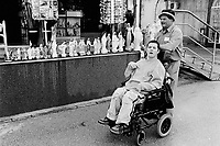 Bosnia. Medjugorje. A father and his handicapped son from Ireland pass in front of tourist shop which sells statues of the Virgin Mary. © 2002 Didier Ruef