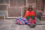 A Peruvian woman sits on the sidewalk in Cuzco.