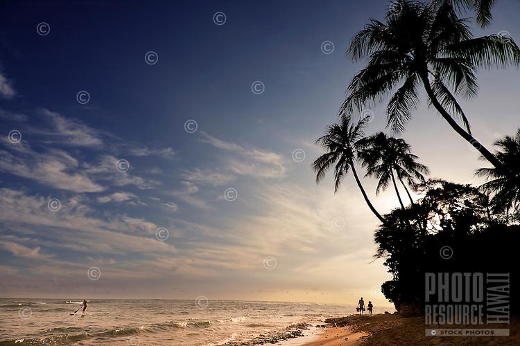 Couple enjoys romantic walk on beach as paddle-boarder enjoys another world-famous Hawaiian sunset.