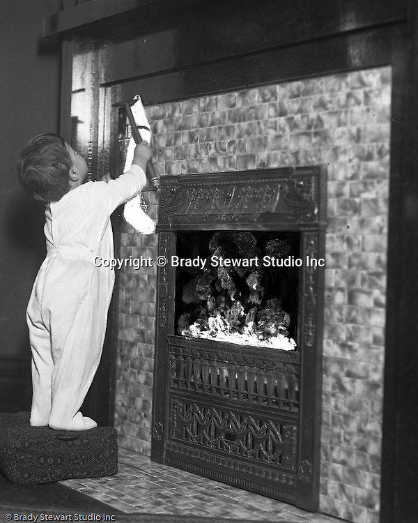 "Wilkinsburg PA:  Helen Stewart hanging a Christmas Stocking.  Brady Stewart etched on the emulsion side of the film to create a ""fire"" effect in the fireplace."