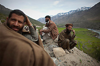 Villagers wait while US Forces investigate and recover a vehicle destroyed by a roadside bomb near Naray in Kunar. A unit of the 3rd Brigade Combat Team, 1st Infantry Division responded to an IED (improvised explosive device) attack on a coalition supply convoy. The bomb destroyed a supply truck carrying Humvee spare parts.