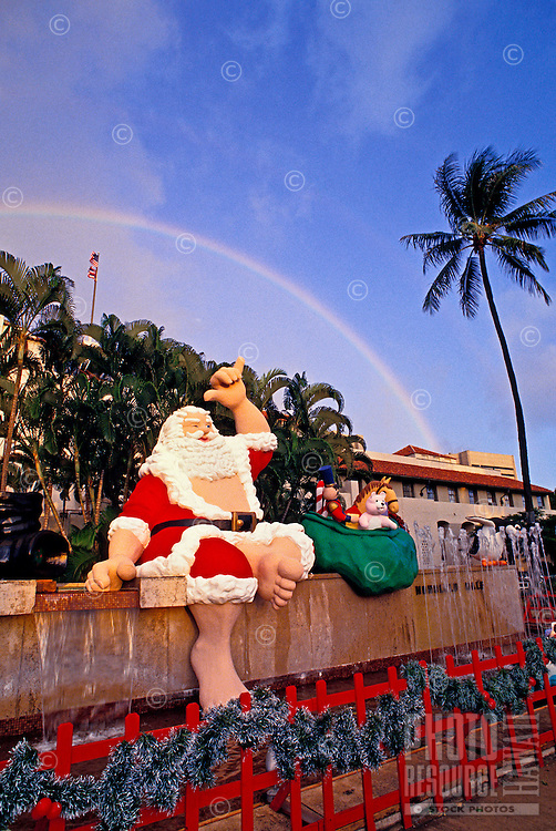 Large Santa Claus sitting on the outside wall at Honolulu Hale flashing shaka sign with a rainbow in background.