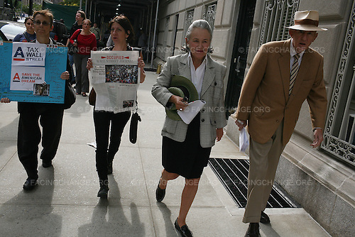 """New York City.October 11th, 2011..An elderly couple walk out of their home as """"Occupy Wall Street"""" protestors march through New York City's wealthy Upper East Side neighborhood to visit the homes of five billionaires, Rupert Murdoch, David Koch, Howard Milstein, John Paulson, and Jamie Dimon, all people who they claimed have not paid their fair share of taxes."""