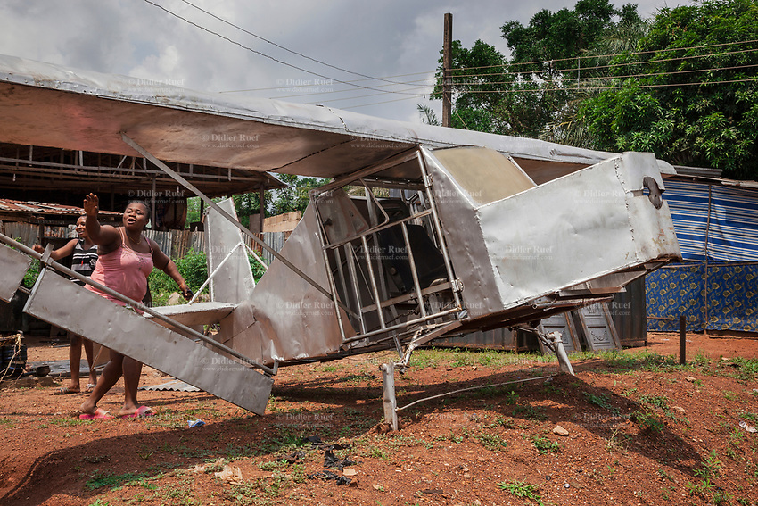 Nigeria. Enugu State. Amechi. The airplane's model was built by Michael Nweze during his free time in order to show to potential customers his craft in welding. Michael Nweze was assisted in his work by a fellow junior welder. Two joyful young women get close to the aircraft. 9.07.19 © 2019 Didier Ruef