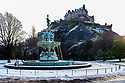 Someone on a solo walk enjoys the first snowfall, in the first Covid Winter, by the Ross Fountain, in Princes Street Gardens, beneath Edinbugh Castle, Edinburgh. Edinburgh has been placed in Tier 4 restrictions due to the Covid-19 pandemic.