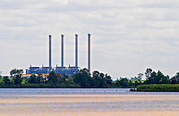 A view from Bourg across the Dordogne river of the oil refinery industrial plant with four chimnies chimney chimneys. It can also be seen from the other side over the Garonne river if one is in Macau Margaux. It marks where Dordogne and Garrone join and become the Gironde estuary  Cotes de Bourg  Bordeaux Gironde Aquitaine France
