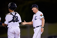 Connecticut Tigers hitting coach Bill Springman (22) goes to the mound to make a pitching change as catcher Gresuan Silverio (13) looks on during a game against the Hudson Valley Renegades on August 20, 2018 at Dodd Stadium in Norwich, Connecticut.  Hudson Valley defeated Connecticut 3-1.  (Mike Janes/Four Seam Images)