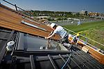 AMERSFOORT - Langs de snelweg A1 in de Amersfoortse wijk Vathorst werken medewerkers van bouwbedrijf De Waal uit Utrecht het dak af van het nieuwe hoofdkantoor van Prénatal. Het Prénatal Hearts Centrum wordt 13.000 m² groot, biedt ruimte aan kantoren en een groot warenhuis en krijgt onder het pand 120 parkeerplaatsen die half in de geluidswal komen te liggen. Het gebouw krijgt onder een stalen kap diverse gezellige houten huisjes met ramen en schuin dak, en zal tevens als geluidsmuur functioneren voor de wijk erachter. Bij de ingang van de winkel kunnen bezoekers door een rond gat in de betonvloeren, dwars door het gebouw naar boven kijken. COPYRIGHT TON BORSBOOM