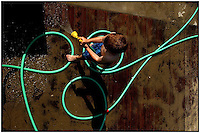 A green water hose makes an interesting series of circles around a young boy as he washes off a deck. Model released.