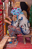 Morocco.  Young Amazigh Berber Girls Working at a Loom.  Ait Benhaddou Ksar, a World Heritage Site.