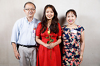 Contestant Nicolette Chin of Singapore, center, poses with host family members Fritz Tai and Carol Tai at a photo booth during the opening reception and dinner of the 11th USA International Harp Competition at Indiana University in Bloomington, Indiana on Wednesday, July 3, 2019. (Photo by James Brosher)