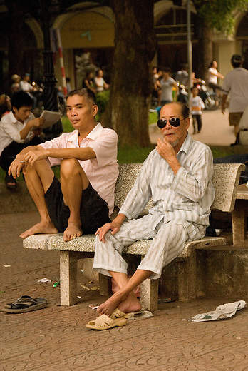 Men lounge in the park around Hoan Kiem Lake wearing their pajamas which is not at all uncommon to see in Vietnam. In the background Tai Chi is being practiced.