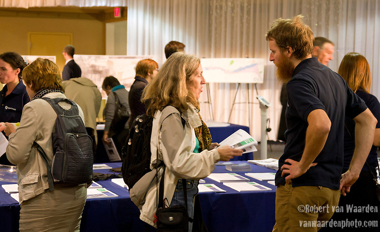 A member of the  SaveCanada team, a group of activists fighting for a cleaner future and against the development of TransCanada's Energy East pipeline speaking with a concerned citizen at TransCanada's open house in Montreal.