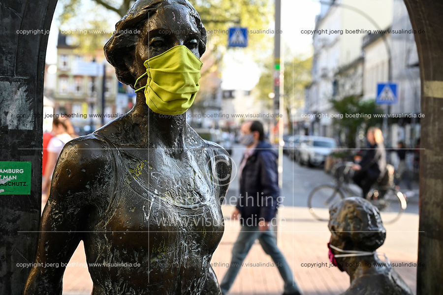 GERMANY, Hamburg, Ottensen, Corona Virus, COVID-19 , Ottenser Torbogen, two women sculpture by artist Doris Waschk-Balz , somebody has put a protective mask to protect them from Covid-19