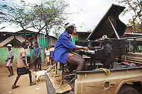"""Ethiopia. Southern Nations, Nationalities, and Peoples' Region. Omo Valley. Turmi. Market day. Hamar tribe (also spelled Hamer). Pastoralist group. Toyota pick-up truck. Marc Vella is a french musician and a nomadic pianist. Over the last 25 years he has travelled with his Grand Piano in around forty countries to celebrate humanity. Thanks to the variacordes which he has devised, his piano music is unique. Creator of """"La Caravane amoureuse"""" (The Caravan of Love) he takes people with him to say """"I love you"""" to others and """"lovingly conquered"""" their hearts and souls. Marc Vella and a Hamar man play an improvised duet-playing - one piano and four hands. The Omo Valley, situated in Africa's Great Rift Valley, is home to an estimated 200,000 indigenous peoples who have lived there for millennia. Amongst them are 60'000 to 70'000 Hamar, an Omotic community inhabiting southwestern Ethiopia. Southern Nations, Nationalities, and Peoples' Region (often abbreviated as SNNPR) is one of the nine ethnic divisions of Ethiopia. 9.11.15 © 2015 Didier Ruef"""