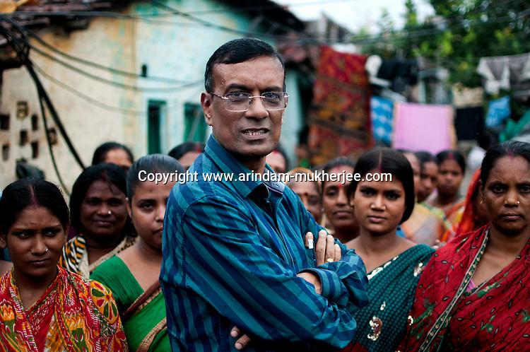 Mr. Chandrashekhar Ghosh, 52,  founder and CMD of  Bandhan Micro finance, surrounded by a group of beneficiaries at Daspara slum, Kolkata, West Bengal, India. Arindam Mukherjee