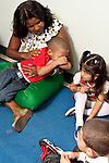 Education preschool first days of school 2-3 year olds crying boy in teacher's lap observed by other children.