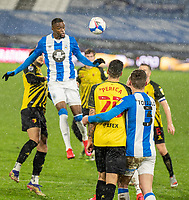 19th December 2020 The John Smiths Stadium, Huddersfield, Yorkshire, England; English Football League Championship Football, Huddersfield Town versus Watford; Harry Toffolo and Stipe Perica of Watford watch as , Isaac Mbenza heads clear