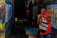 "José Corredor (""Runner"") cleans paint from his brushes in the sign painting workshop in Cartagena, Colombia, 14 April 2018. Hidden in the dark, narrow alleys of Bazurto market, a group of dozen young men gathered around José Corredor (""Runner""), the master painter, produce every day hundreds of hand-painted posters. Although the vast majority of the production is designed for a cheap visual promotion of popular Champeta music parties, held every weekend around the city, Runner and his apprentices also create other graphic design artworks, based on brush lettering technique. Using simple brushes and bright paints, the artisanal workshop keeps the traditional sign painting art alive."