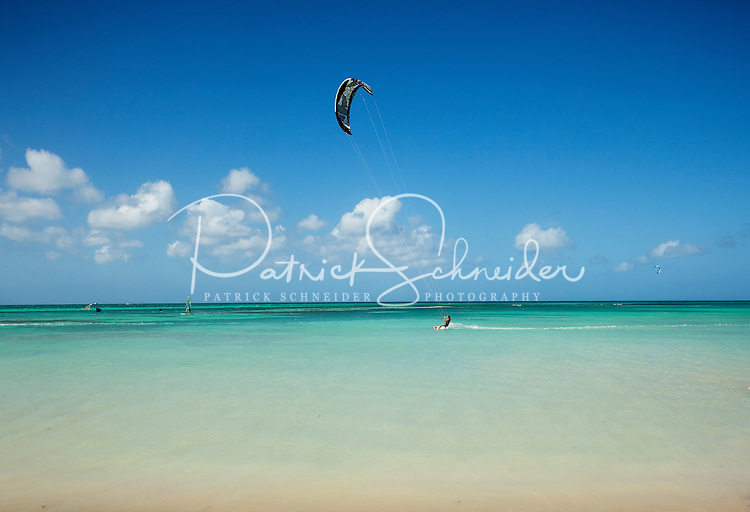 Kite boarders catch the strong winds of the Caribbean Sea and make waves in Aruba. One of the newer watersports available today, kite boarding uses large, inflatable kites harnessed to participants by rope. Standing atop small surfboards with footstraps, the kite boarders can skim the water's surface up to 30 miles per hour and are able to jump high into the air.  Aruba remains a popular tourist destination, with international planes and cruise ships arriving daily. Aruba, part of the Lesser Antilles, is famous for its white sand beaches, blue/green waters and mild climate.