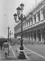 1966 file<br /> <br /> In happier days St. Mark's Square was a pleasant place to idle away a few hours. Then came the rains and flooding - the worst in Italy for a thousand years. White line on ornamental lamp standard shows how high the waters rose.