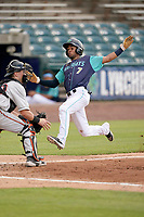 Second baseman Yordys Valdes (7) of the Lynchburg Hillcats slides home safely with a run in a game against the Delmarva Shorebirds on Wednesday, August 11, 2021, at Bank of the James Stadium in Lynchburg, Virginia. Defending is catcher Logan Michaels (10). (Tom Priddy/Four Seam Images)