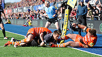 Chris Wyles of Saracens  forces his way past Tom Youngs and Freddie Burns of Leicester Tigers to score a try in the corner during the Aviva Premiership Rugby match between Saracens and Leicester Tigers at Allianz Park on Saturday 11th April 2015 (Photo by Rob Munro)