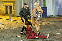 Pictured: A woman is helped to her feet by a man and a woman. Friday 14 December 2018<br /> Re: Revellers in Wind Street, Swansea, Wales, UK.