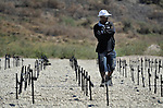 A man walks through a field of crosses marking the site where the bodies are buried of more than 100,000 victims from the January 2010 earthquake. More than 230,000 people were killed in the quake. Additional bodies have been added since November 2010 to the grave since a cholera epidemic swept through poor neighborhoods of Haiti, killing more than 3,600 people...