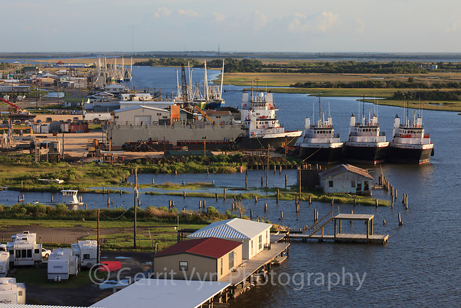 Boats and development along the road to Grand Isle in the Mississippi River delta. Plaquemines Parish, Louisiana. July 2010.