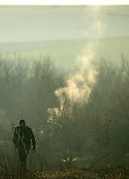 A man looks at white smoke of a fire underground in the national park of Las Tablas de Daimiel, in Ciudad Real on November 16, 2009. The European Union launched an investigation into Spanish wetland that has turned bone dry through mismanagement of water resources  from areas where fish once swam. The EU wants the Spanish government to explain how it plans to save Las Tablas de Daimiel National Park.The park, one of Spain's few wetlands, is classified as a UNESCO biosphere site and an EU-protected area because of its birdlife. But it has been drying up for decades, largely because of wells dug by farmers on the edges of the park to tap an aquifer that feeds the wetland's lagoons. Many of the wells are illegal.   (c)Pedro ARMESTRE