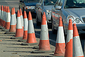 Traffic cones and cars on a road in North London.