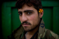 An Afghan National Army (ANA) soldier, with a flower behind his ear at Camp Blessing in the Pesh Valley.