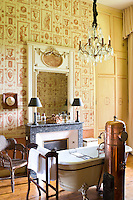 A wonderfully opulent bathroom, lit by a chandelier and with hot water provided by an antique copper brazier