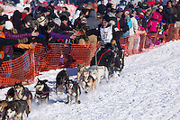 Sunday, March 4, 2012  Scott Janssen high fives spectators as he moves along the starting chute during the restart of Iditarod 2012 in Willow, Alaska.
