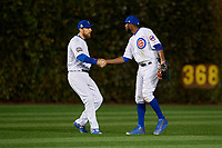 Chicago Cubs outfielders Ben Zobrist (18) and Dexter Fowler (24) celebrate closing out Game 5 of the Major League Baseball World Series against the Cleveland Indians on October 30, 2016 at Wrigley Field in Chicago, Illinois.  (Mike Janes/Four Seam Images)
