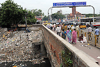 River  is covered with rubbish and very polluted.  People are passing by on bridge in Madras, India.