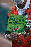 A Greensboro Grasshoppers usher holds a sign reminding patrons to wear a mask during the minor league baseball game against the Hickory Crawdads at First National Bank Field on May 6, 2021 in Greensboro, North Carolina. (Brian Westerholt/Four Seam Images)