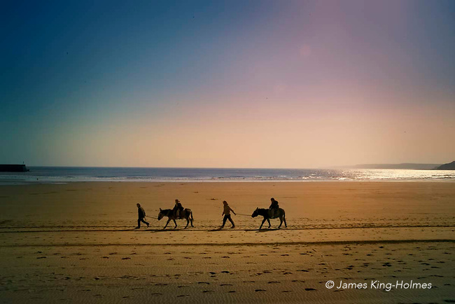 Children's donkey ride on the beach at Scarborough, England in early April. Cool weather has left the beach deserted in spite of the spring sunshine.