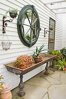 Antique iron sink used as planter outdoors on the patio next to house, with Begonia in container garden, Bromeliad houseplants, other antiques hanging on wall as rustic ornaments