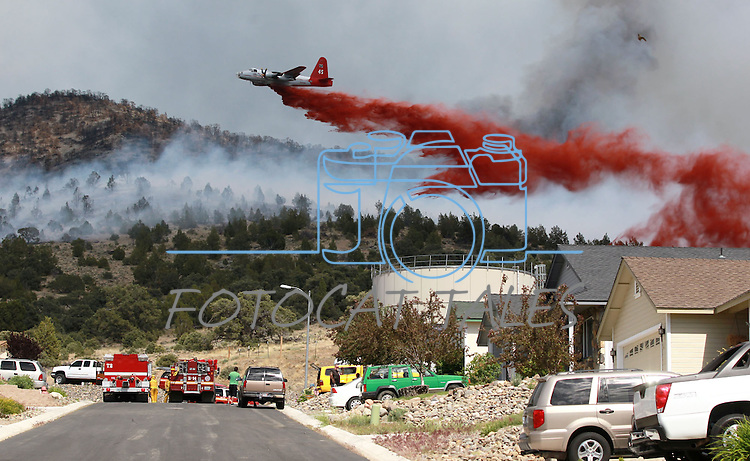 An airtanker drops retardant near houses in the Ray May subdivision off Highway 395 south of Gardnerville on Friday afternoon, June 1, 2012, after multiple brush fires were started in the area by lightning. .Photo by Cathleen Allison/Nevada Photo Source