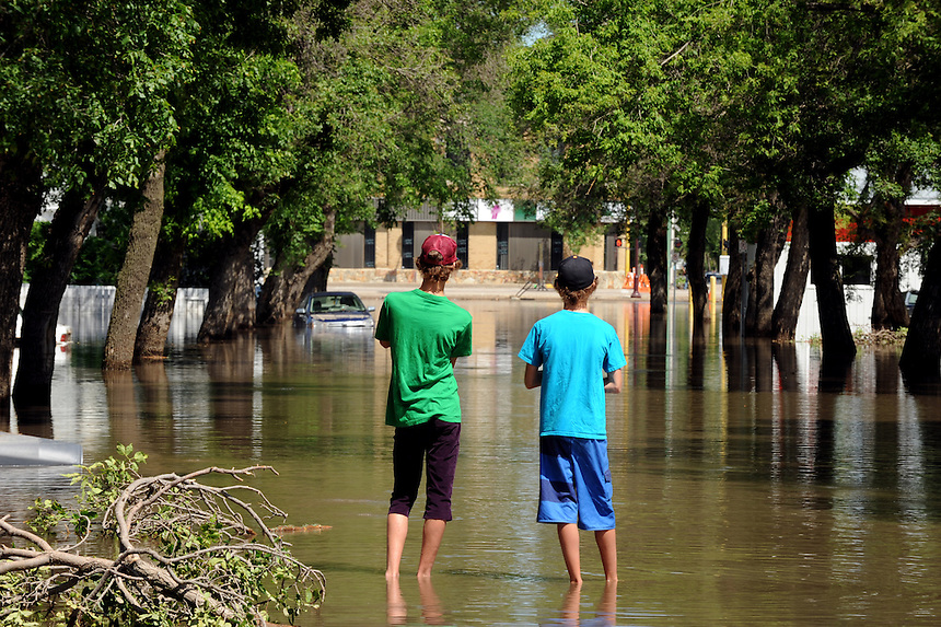 Two boys check out the flooding on Agricultural Street in Yorkton, Saskatchewan on Friday, July 2, 2010. THE CANADIAN PRESS/Mark Taylor.