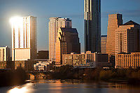 Austin's ultra modern skyline is composed of all glass skyscrapers and buildings as water sports enthusiast navigate Lake Austin in kayaks, canoes, and rowing shells